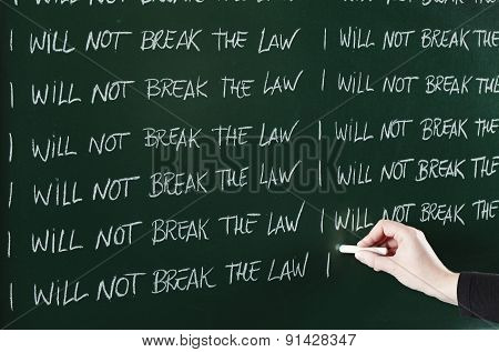 I will not break the law sentence written repeatedly on blackboard as a punishment