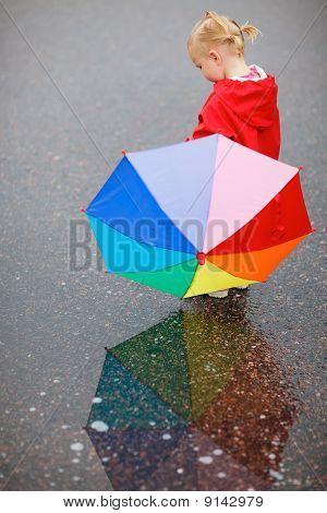 Kinder Kleinkind Mädchen mit bunten Sonnenschirm an regnerischen Tag