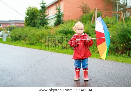 Toddler Girl With Umbrella Outside On Rainy Day