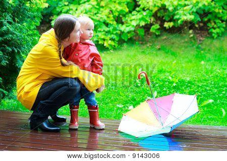 Mãe e filha ao ar livre em dia chuvoso