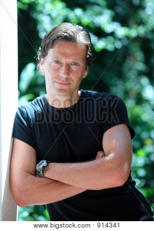 Handsome Middle Aged Man Leaning Against Wall In The Sun