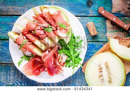 Salad Of Melon With Thin Slices Of Prosciutto, Arugula Leaves And Balsamic Sauce Top View