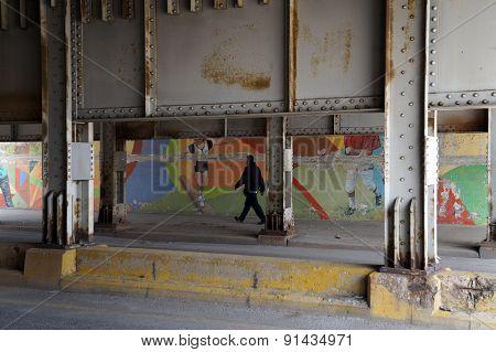 Man Walking Through an Underpass