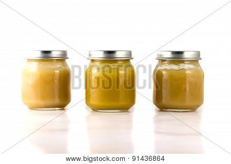 Three jars of fruit puree in a row