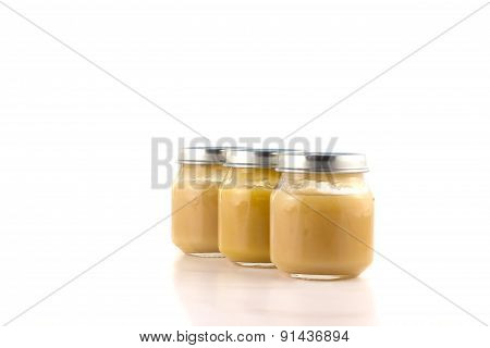 Three jars with fruit puree each other in an oblique row