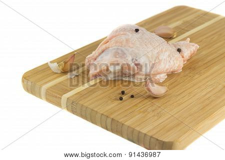 Chicken thighs on wooden board in a sauce with pepper and garl