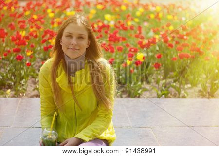 Girl Sitting Next To A Flower Bed