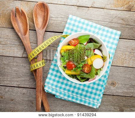 Fresh healthy salad on wooden table and kitchen utensil. View from above with copy space
