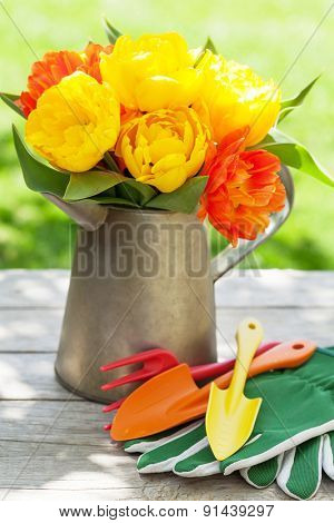 Colorful tulips and garden tools in sunny garden