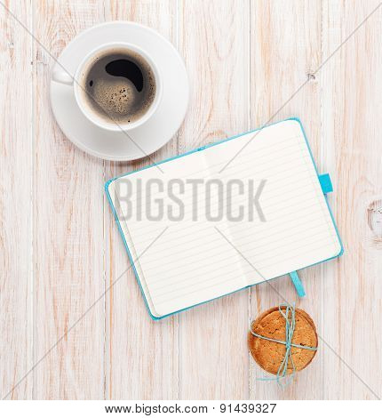 Coffee, cookies and notepad on white wooden table with copy space