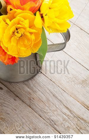 Colorful tulips bouquet in watering can on wooden table