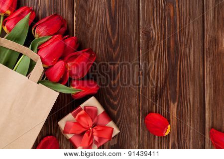 Red tulips bouquet in paper bag and gift box over wooden table background with copy space