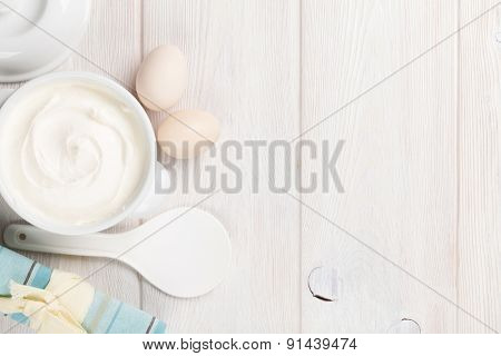 Sour cream in a bowl and eggs on wooden table. Top view with copy space