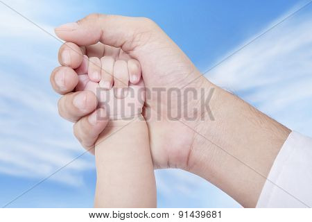 Baby Hand On The Father Palm
