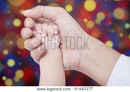 Father Hand Holds His Baby Hand