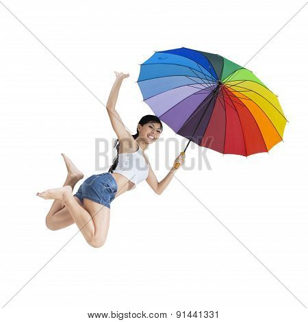 Woman Jumping With A Rainbow Umbrella