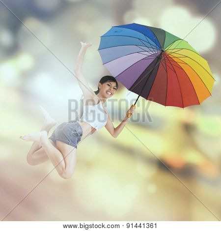 Woman Jumps Over Light Glitter Background