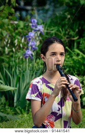 Little Girl Plays the Recorder in a Garden