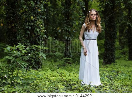 Art fashion portrait of young woman walking in the woods