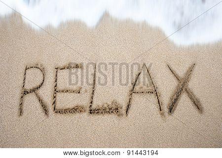 Relax Word Handwritten In Sand On Beach