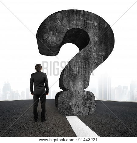 Man Looking At Huge 3D Concrete Question Mark Asphalt Road