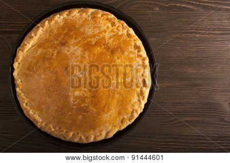 homemade pie with a stuffing on a wooden table
