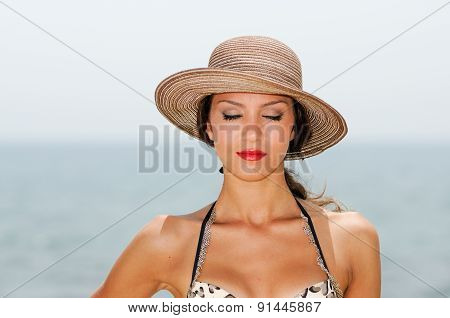 Attractive Woman With A Sun Hat On A Tropical Beach, Eyes Closed