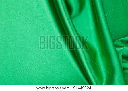 Green silk cloth texture closeup.