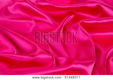 Soft folds of pink silk cloth texture.