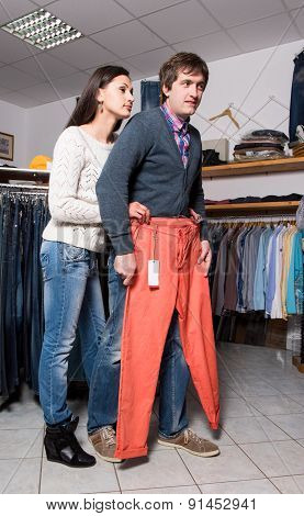 Shop assistant showing jeans to man