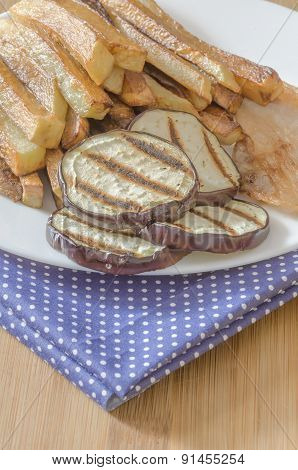 Fries potatoes with grilled eggplant on wooden background