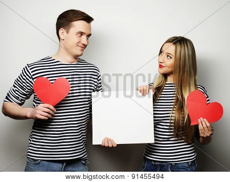couple, love and family concept: happy couple holding white blank and red hearts.