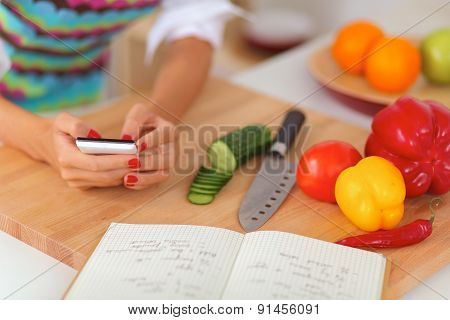 Smiling young woman preparing salad in the kitchen