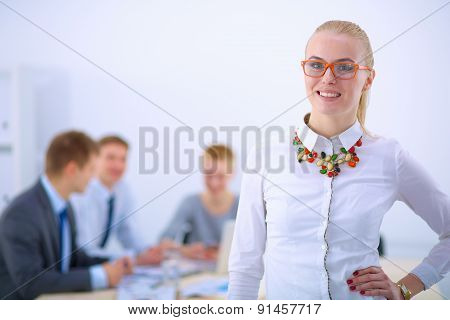 Portrait of a young woman working at office standing with folder
