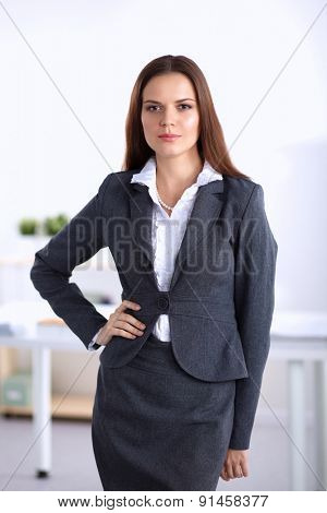 Portrait of business woman standing with crossed arms in office .
