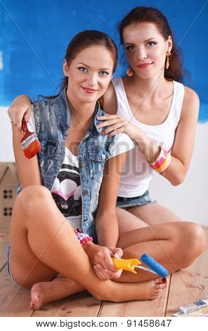 Two Beautiful young woman doing wall painting, sitting.