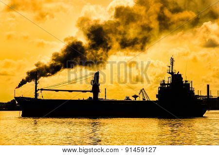 Oil refinery releasing a huge smoke column polluting the air with the silhouette of a ship on the foreground
