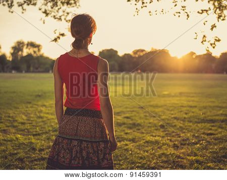 Woman Standing In Park Admiring The Sunset