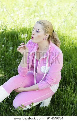 the beautiful girl in a pink suit blows on a dandelion