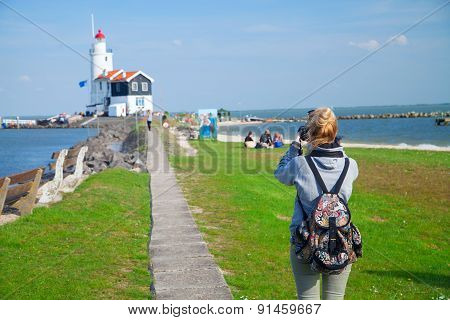 Girl Shoots Video At The Lighthouse On The Sea
