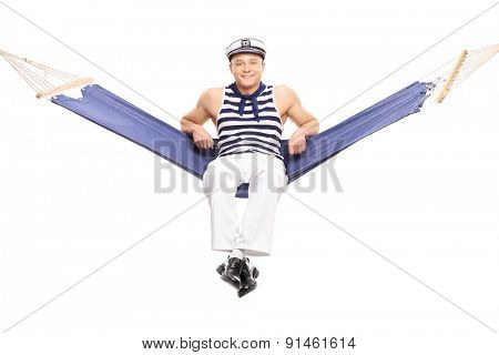 Studio shot of a relaxed young sailor sitting on a hammock and smiling isolated on white background