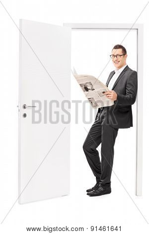 Businessman reading a newspaper and leaning on an open door. The newspaper is custom made, the pictures are my copyright. You can find them and the necessary Model Releases attached to the photograph