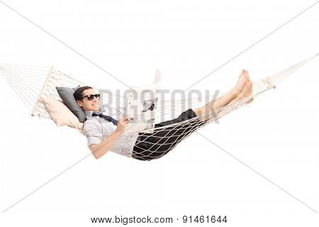 Relaxed man reading a newspaper and lying in a comfortable hammock.newspaper is custom made the pictures are my copyright. You can find them and the necessary Model Releases attached to the photograph