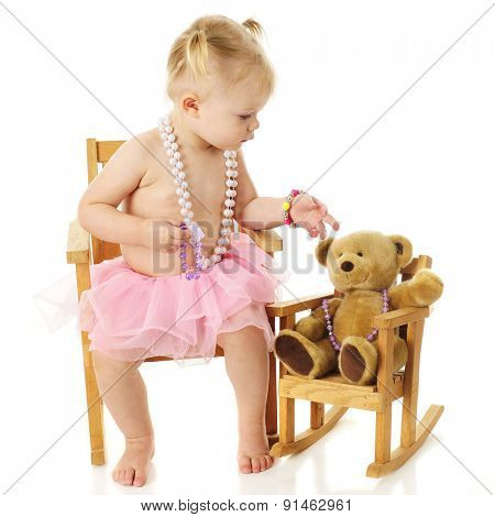 An adorable 2 year old checking to see if her toy bear has the right jewelery.  On a white background.