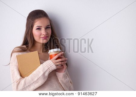 Portrait of a young woman with cup of tea or coffee, isolated