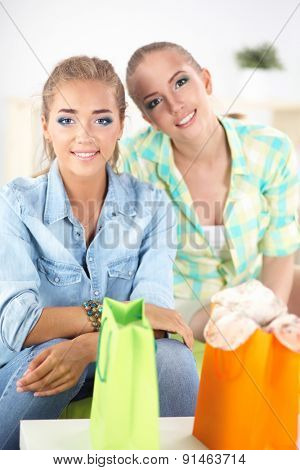 Two young women sitting with shopping bag at home .