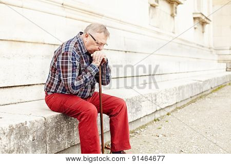 Portrait of pensive mature man in glasses and plaid shirt resting leaning on his wooden walking stick