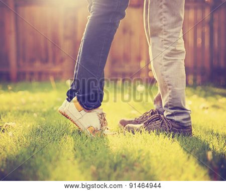 A young couple kissing in a backyard in summer sun light during sunset with dandelions blooming toned with a retro vintage instagram filter (VERY SHALLOW DOF on legs)