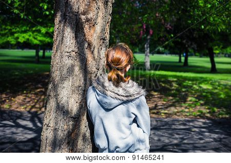 Young Woman Resting By Tree In Park