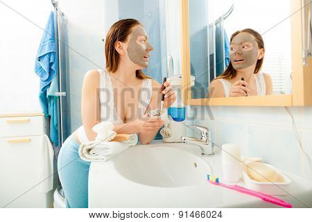 Woman Applying Mud Facial Mask